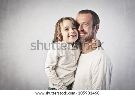 Smiling young man holding his daughter in his arms