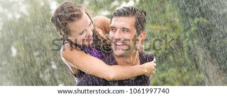 Smiling young man holding pretty girlfriend on his back during heavy summer rain