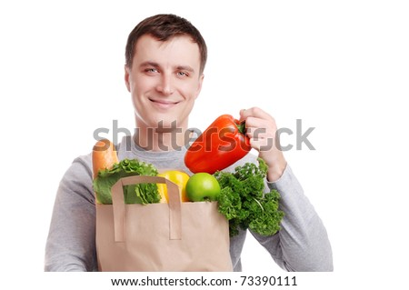 smiling young man holding shopping bag full of groceries on white