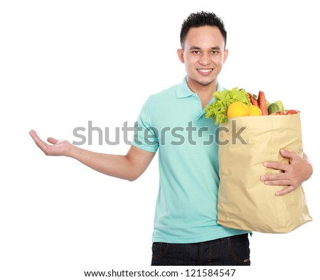 smiling young man holding shopping bag full of groceries presenting copyspace