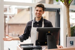 Smiling young man in apron standing at the cash register indoors