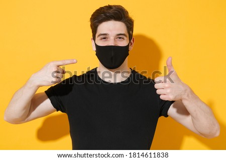Smiling young man in black t-shirt pointing on sterile face mask to safe from coronavirus virus covid-19 during pandemic quarantine showing thumbs up isolated on yellow background studio portrait.