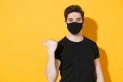 Smiling young man in black t-shirt sterile face mask to safe from coronavirus virus covid-19 during pandemic quarantine pointing finger aside workspace isolated on yellow background studio portrait.