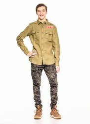Smiling young man in camouflage clothing. Happy  Conscript in camouflage, isolated. Cheerful rookie in army clothes. Teenager in khaki military clothing poses in a studio on a white background.