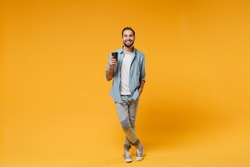 Smiling young man in casual blue shirt posing isolated on yellow orange wall background studio portrait. People sincere emotions lifestyle concept. Mock up copy space. Hold paper cup of coffee or tea