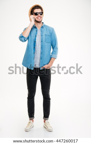 Smiling young man in hat and sunglasses standing and talking on mobile phone over white background