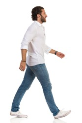 Smiling young man in jeans, sneakers and white shirt is walking and looking away. Side view. Full length studio shot isolated on white.