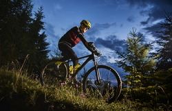 Smiling young man in sports cycling suit riding bicycle downhill with beautiful blue sky on background. Male bicyclist wearing safety helmet and glasses while cycling down grassy hill at night.