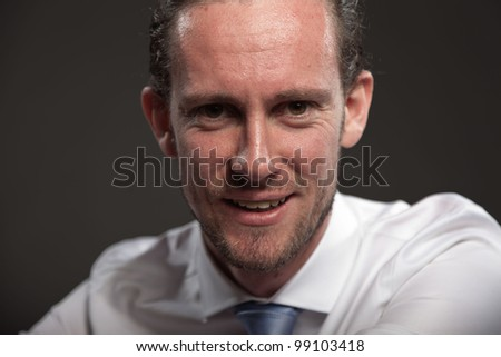 Smiling young man long hair with expressive face wearing white shirt and blue tie. Isolated on grey background.