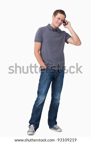 Smiling young man on his cellphone against a white background