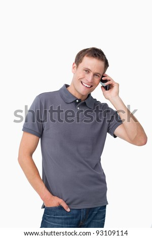 Smiling young man on his mobile phone against a white background