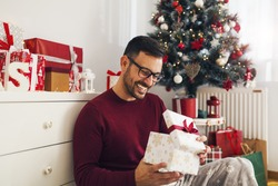 Smiling young man opening Christmas gift at home
