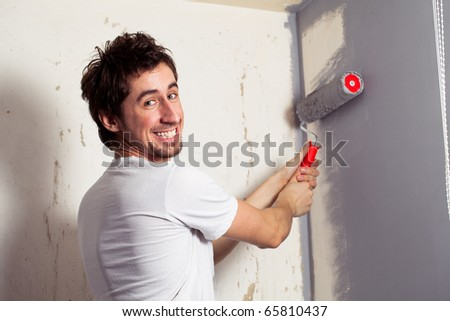 Smiling young man painting the wall