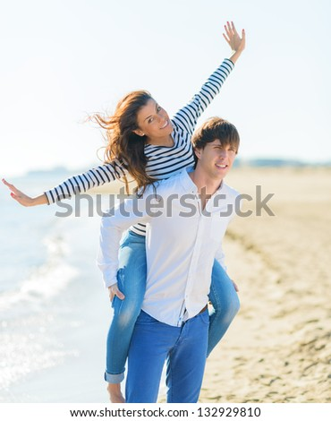 Smiling Young Man Piggybacking His Pretty Girlfriend