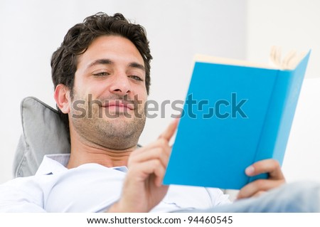 Smiling young man reading a novel book while relaxing on sofa