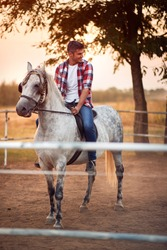 Smiling young man rides a horse on a farm. hobby time, riding.