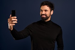 Smiling young man 30s in casual black high neck sweate posing isolated on Pacific Blue background. People sincere emotions lifestyle concept. Mock up copy space. Doing selfie shot on mobile phone.