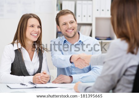 Smiling young man shaking hands with an insurance agent or investment adviser as he sits in a meeting with his wife in her office - stock photo