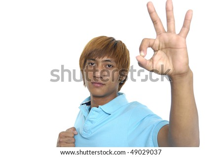Smiling young man showing OK sign.