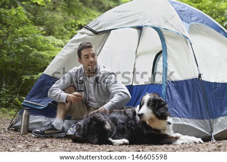 Smiling young man sitting by tent with his pet dog