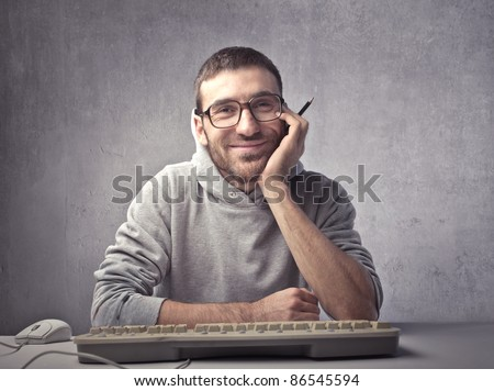 Smiling young man sitting in front of a computer keyboard