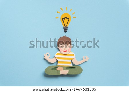 Smiling young man sitting in lotus pose and meditating. Teen with lightbulb concentrating on new idea for solution of important question. Hand cut illustration from paper