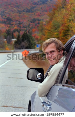 Smiling young man sitting in the car