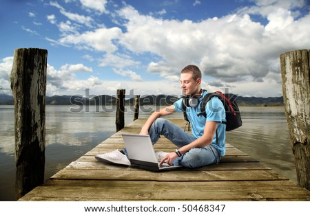 Smiling young man sitting on a dock and using a laptop