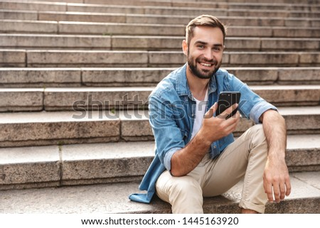 Smiling young man sitting on stairs outdoors, using mobile phone