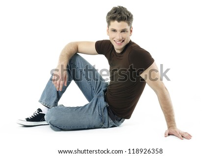 smiling young man sitting on the floor on white background