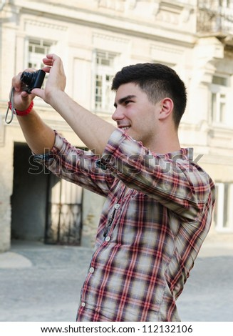 Smiling young man standing outdoors in an urban environment taking a photograph
