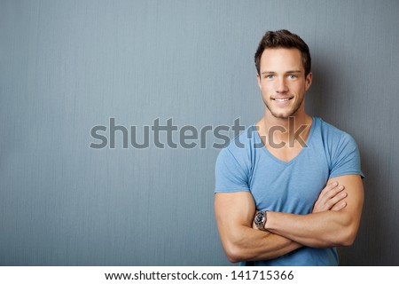 Smiling young man standing with arms crossed against gray background