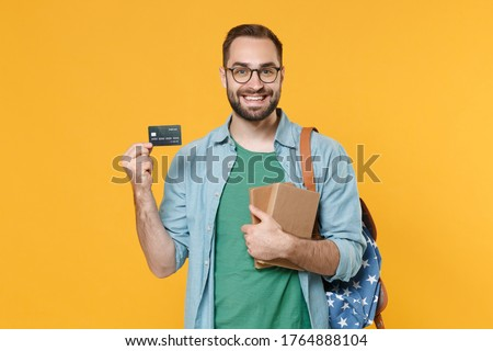 Smiling young man student in casual clothes glasses backpack hold books isolated on yellow background. Education in high school university college concept. Mock up copy space. Hold credit bank card Foto stock ©