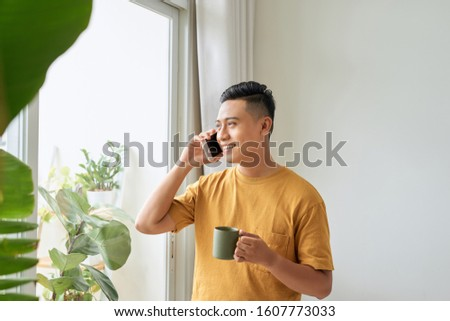 Smiling young man talking on mobile phone, looking at the window at home