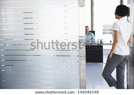 Smiling young man talking to woman standing in doorway at his office