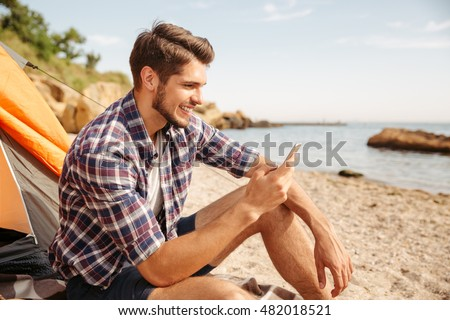 Smiling young man tourist using smartphone sitting in touristic tent at the beach