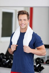 Smiling young man training in the gym with towel around his neck