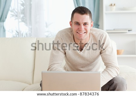 Smiling young man using a notebook in his living room