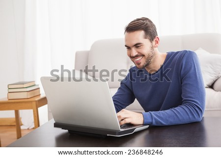Smiling young man using his laptop at home in the living room