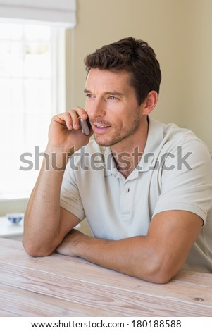 Smiling young man using mobile phone at home