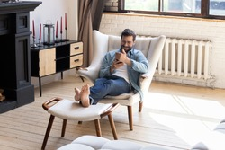 Smiling young man using smartphone, sitting in armchair in modern living room, happy male holding phone, looking at screen, chatting in social network or shopping online, playing game, using apps