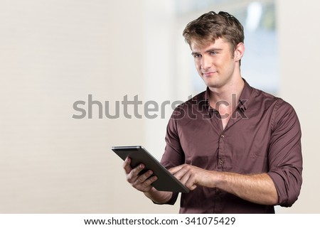 Smiling young man using tablet computer #341075429