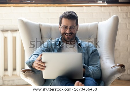 Smiling young man wearing glasses using laptop, sitting in cozy armchair, happy male looking at computer screen, chatting in social network or shopping online, playing game, working at home