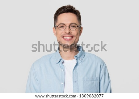 Smiling young man wearing shirt and glasses looking at camera, millennial guy nerd isolated on white grey studio blank background, funny male student geek in spectacles with happy face portrait