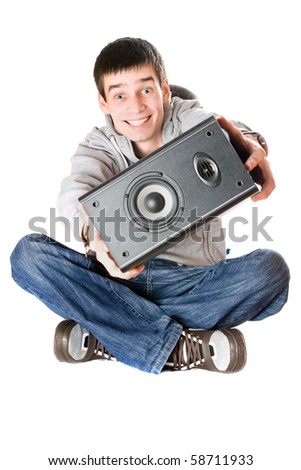 Smiling young man with a speaker in his hands