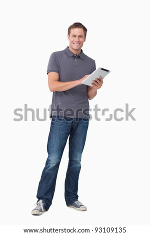 Smiling young man with his tablet computer against a white background - stock photo
