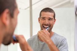 Smiling young man with toothbrush cleaning teeth and looking mirror in the bathroom. Handsome man brushing his teeth in morning in bathroom. Happy guy in pajamas brushing teeth before going to sleep.