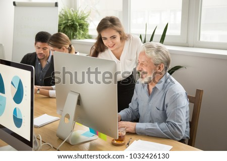 Smiling young manager helping senior worker with funny computer work in office, mentor teacher training happy older employee at workplace, colleagues of different age laughing looking at pc monitor