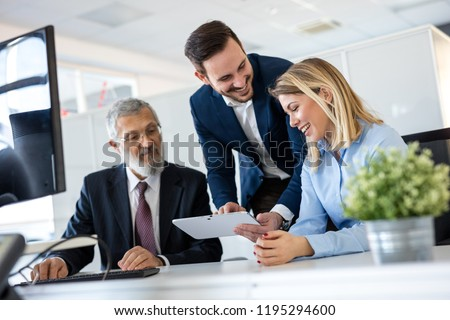 Smiling young manager helping senior worker with funny computer work in office, mentor teacher training happy older employee at workplace, colleagues of different age laughing looking at pc monitor.
