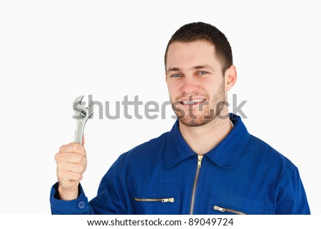 Smiling young mechanic holding his wrench against a white background